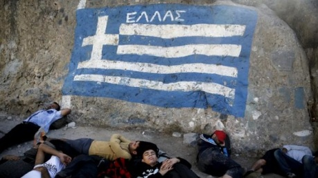Syrian refugees sleeps under a graffiti depicting the Greek national flag as they wait for a registration procedure at the police and coast guard station on the eastern island of Agathonisi, Greece, September 10, 2015. Agathonisi, a tiny island with fewer than 200 residents, receives about 300 to 600 refugees and migrants every day, local authorities estimated. Most of the people flooding into Europe are refugees fleeing violence and persecution in their home countries who have a legal right to seek asylum, the United Nations said on Tuesday. REUTERS/Alkis Konstantinidis