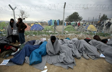 Refugees and migrants who entered Macedonia illegally and were detained by the police, wait to be returned to Greece at a checkpoint on the border line near southern Macedonia's town of Gevgelija, Monday, Feb. 29, 2016. Macedonia is restricting the entry of refugees to match the number of those leaving the country, allowing in only refugees from Syria and Iraq, in response to bottlenecks further up along the Balkans migrant route. (AP Photo/Boris Grdanoski)